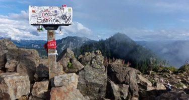 a mailbox, covered in graffiti, atop a mountain