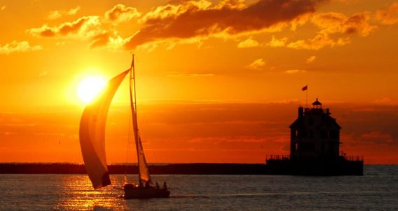silhouette of a sailboat and a lighthouse against a brilliant burnt orange sky