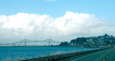 The Astoria-Megler Bridge spans across the Columbia River, town hangs from a hillside to the south, all the while puffy white clouds abound.