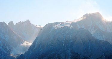 hazy mountain peaks jut craggy into a wide blue sky