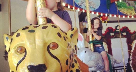 two young boys ride a beautiful, handmade carousel