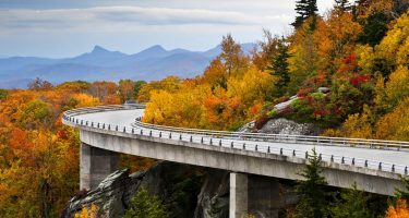 a two lane road curves around a mountain draped in autumn's regalia
