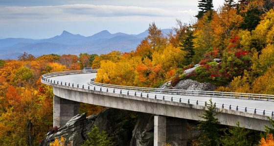 a two lane road curves around a mountain draped in autumn's regalia