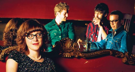 a woman dressed old fashioned and wearing thick rimmed glasses, sits in a plush red lounge seat, three men reflecting in a mirror behind her