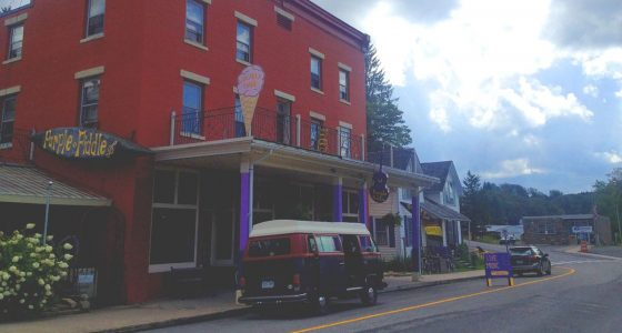 a red brick building on the corner of a main street, a VW bus parked out front