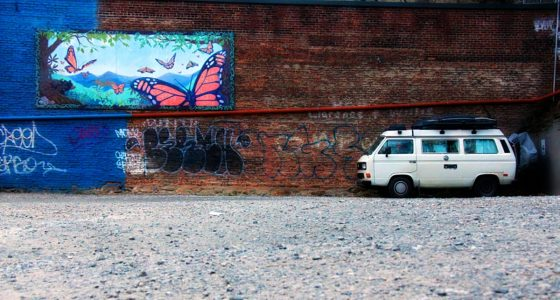 a small, white 1987 Vanagon parked against a brick wall