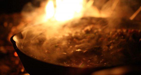 cast iron skillet over a campfire